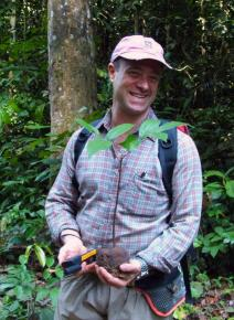 Michael Keller is a research physical scientist with the International Institute of Tropical Forestry in Rio Piedras, Puerto Rico. Michael is standing in the middle of a forest, holding a sapling tree in his hands.