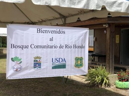 White banner with the words Welcome to the Rio Hondo Community Forest written in Spanish