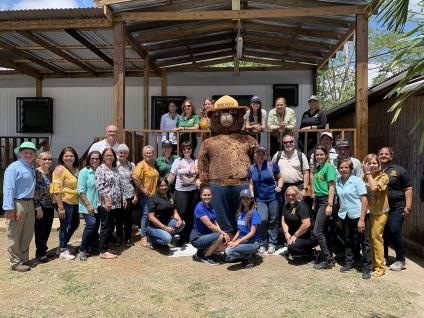 Group picture of Rio Hondo Community board of directors and personnel from IITF posing around a Smokey Bear giant stuffed bear