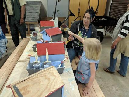 Woman at table building a birdhouse with a young girl