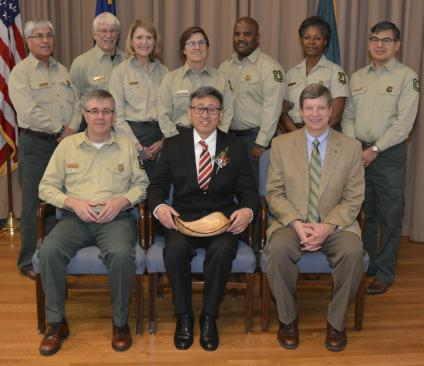 A picture of Ge Sun receiving a Chief's Award, photographed with all the members of the Forest Service executive leadership team in uniform.