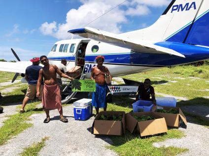 Five men offloading boxes of food supplies from a small private plane