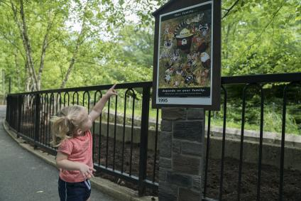 A picture of a child pointing to a Smokey Bear poster in the Smokey Bear Zone at the Smithsonian's National Zoo.