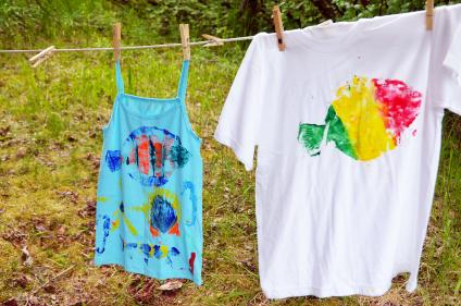 Shirts with painted fish designs hanging from a clothesline