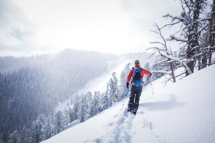 A picture of a person snowshoeing side hill on a snow covered mountain.