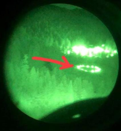 Night vision image of Wolf Creek JC firefighters forming a light ring for helicopter to land