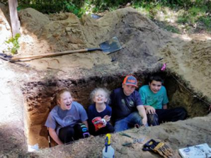 Four children playing inan archeology dig site