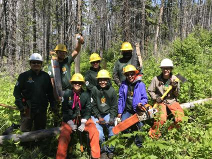 A group of smiling trail workers in a forest wearing hard hats and holding trail-building tools.