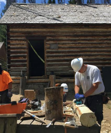 Log cabin being remodeled by workers