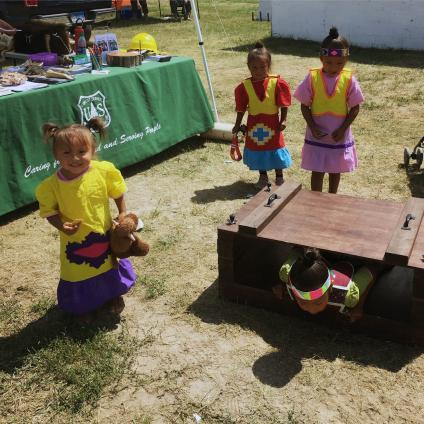 Group of four sisters playing at a Forest Service station at the Oglala LAkota NAtion Powwow