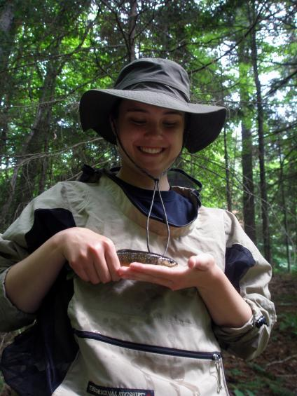 Hutton Scholar Madi Taychert holding a brook trout as part of a fish survey during her time on the Ottawa National Forest.