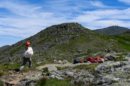 A crewmember carries rocks to the work site on Crawford Path, New Hampshire, with the summit of Mount Washington in the background