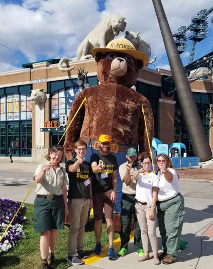 FS employees pose in front of Smokey Bear giant inflatable baloon