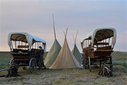 Two wagons and three tipis set up on a grassy plain at the BLM's National Trails Interpetive Center.