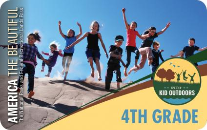 A picture of several kids running and jumping down a dirt or sand covered hill.