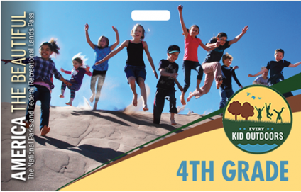 A picture showing a group of kids running and jumping down a sand/dirt covered hill area.