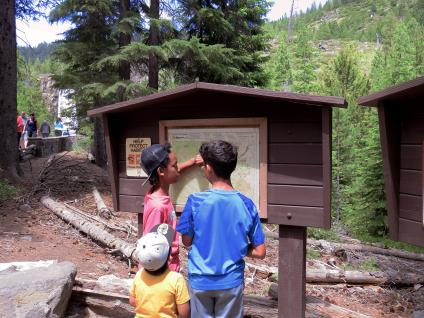 Three kids study trail map on informational sign board.