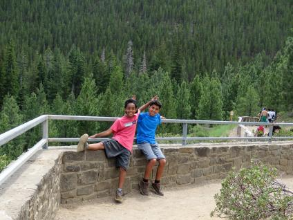 Two kids give each other bunny ears while stopped at a scenic overlook.