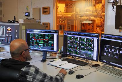A picture of a bioenergy control room, showing several computer screens with displays up, at Honey Lake Power.
