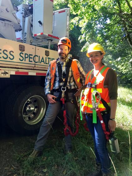 Miriam Smith and a Forest Service employee stand next to an under-bridge inspection truck.