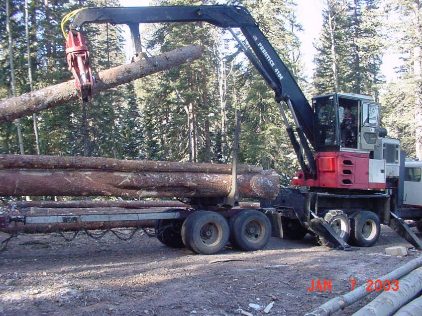 A picture of a front loader stacking logs on a log truck.