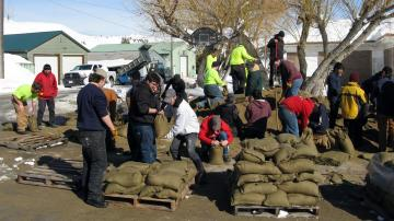 Students filling and stacking sandbags.