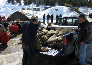 Students load sandbags into back of a pickup truck.