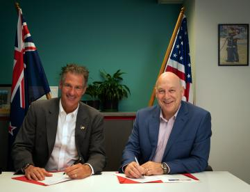 New Zeraland chief fire executive and US ambassador to New Zealand, sitting at desk, signing agreement. NZ and US flags in the background.