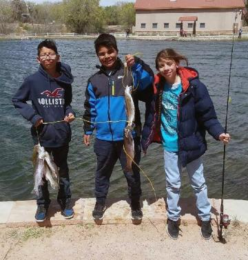 Three kids showing the trouts they caught