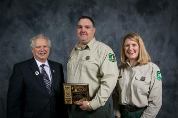 A man in a suit and a woman in Forest Service uniform present an award to second man, also in Forest Service uniforma second man