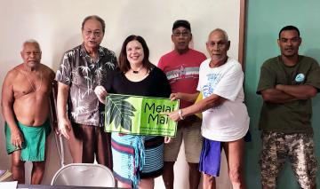 Group photo of five men and one woman; the woman is holding a sign that reads Melai Mai