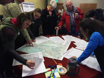 Group of people looking at land maps