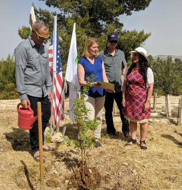Chief Christiansen addressing a gathered crowd at a tree planting ceremony. Three other people, two men and one woman, accompany her.