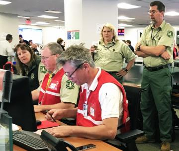 Forest Service members working at a desk during operation Shaken Fury 19