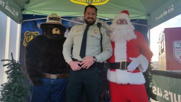 A picture of Officer Matthew Jemmett with Smokey Bear and Santa Claus at a Capitol Christmas Tree event in 2017.