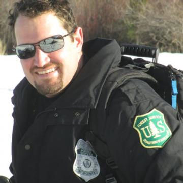 A picture of Matt Jemmett, wearing sunglasses, with a jacket displaying the U.S. Forest Service insignia and law enforcement badge.