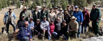 A picture of 24 people, including serveral Forest Service employees in uniform, and one dog standing or kneeling for a group photo.