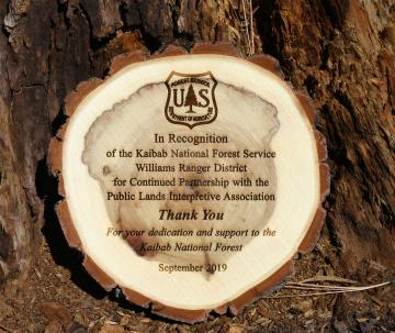 Wooden appreciation plaque leaning up against tree stump.