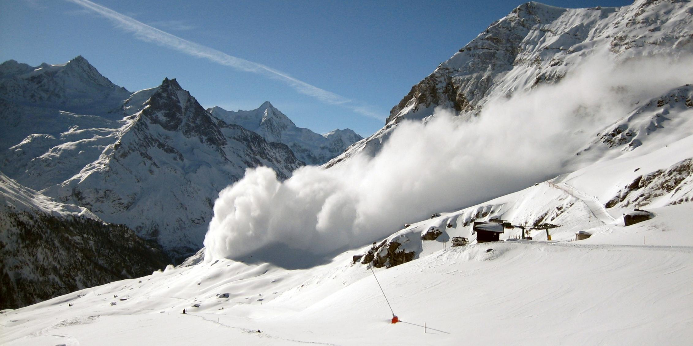 A picture of an avalanche coming down a snow-covered mountain side.