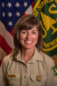 Portrait photo: Heather Provencio in uniform in front of American and Forest Service flags.