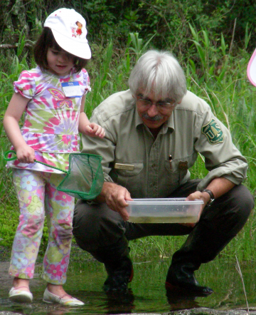 A photo of a forest service employee and little girl looking at a fish in a creek