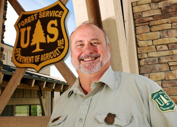 A photo of Chip Weber standing in front of the Forest Service insignia.