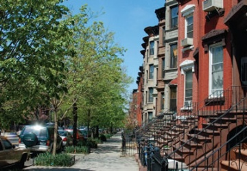 A photo of urban street with rowhouses.