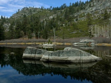 Lake Margaret, located south of the Lake Tahoe Basin, featuring the lake, two large boulders protruding from the water in the foreground, with conifer trees, a rocky mountain ridge, and blue sky in the background.Photo Credit: Tim Rains, U.S. Forest