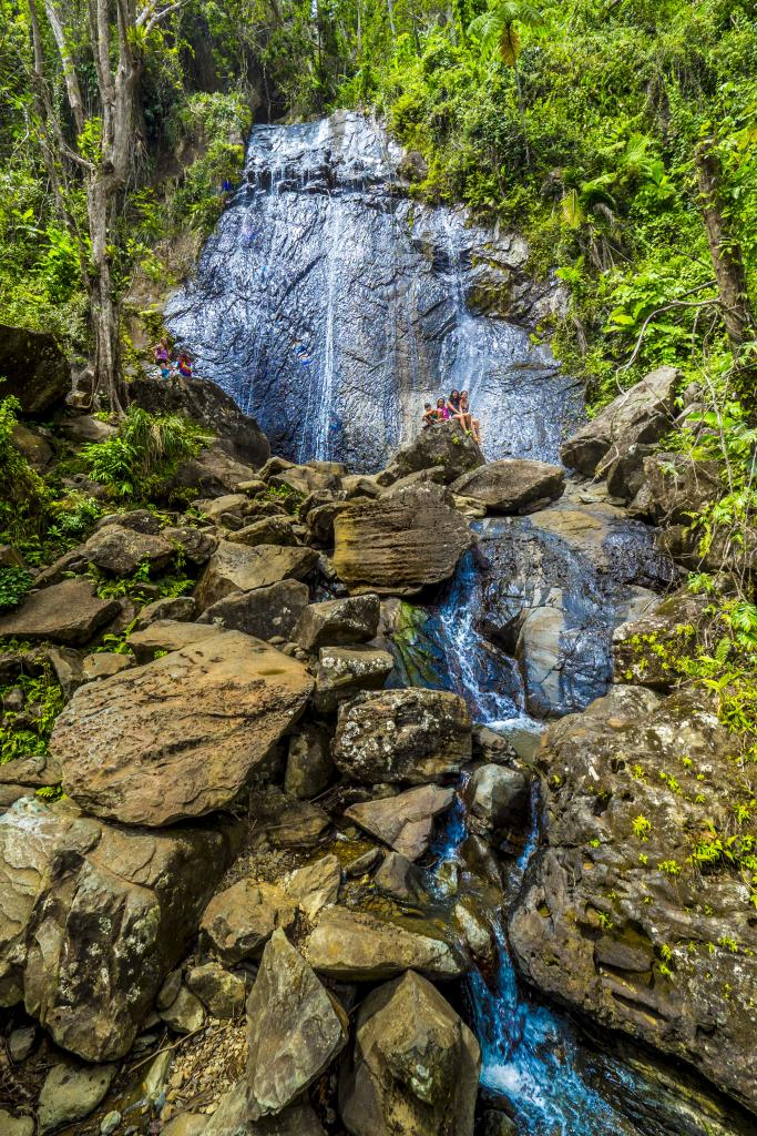 Six months after Hurricane Maria, only a small portion of El Yunque National Forest, Puerto Rico, is available for enjoyment. Here, tourists enjoy climbing La Coca Waterfall. USDA Photo by Preston Keres.