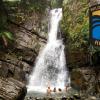 A photo of three people under a waterfall in Rio de la Mina - Puerto Rico