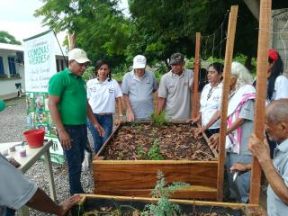 A picture of several adults gathered around a raised garden bed.