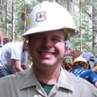 A photo of Forest Service specialist Tom Davis holding up his dirty gloves.