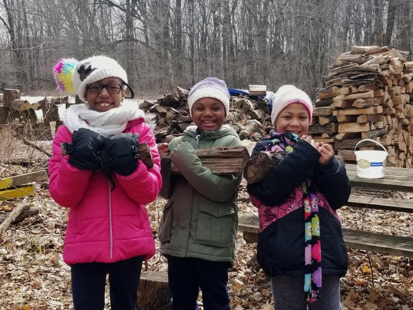 three little girls carrying firewood and smiling