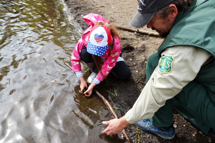 Forest Service personnel helps little girl catch a fish during Fishing day